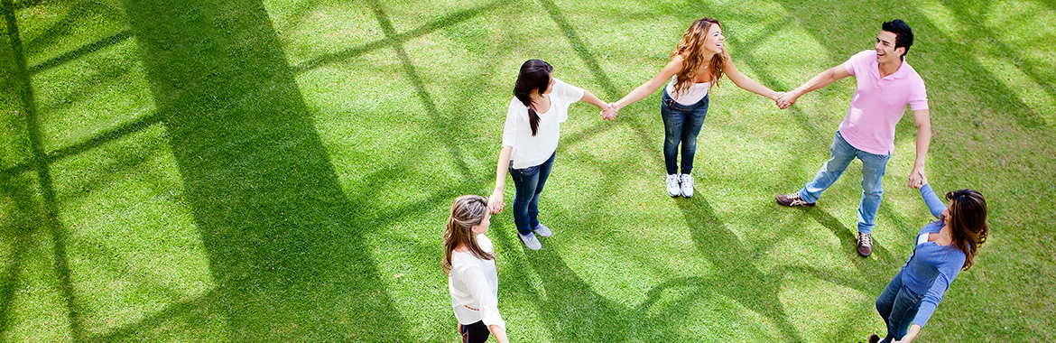 young adults in a circle holding hands
