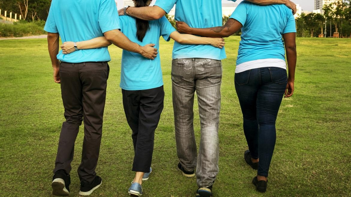 Volunteers walk together with arms around each other