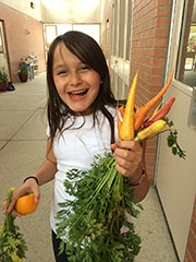 young girl holding carrot and smiling
